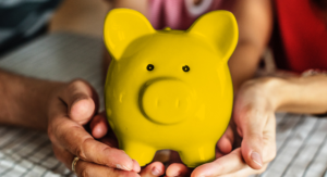 two hands holding yellow piggy bank