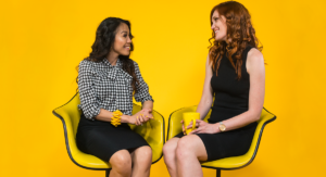 Two businesswomen sitting on yellow chairs and smiling, talking